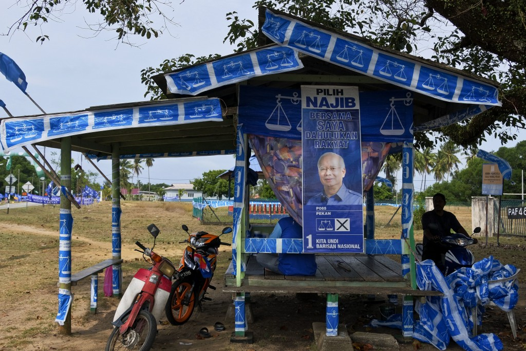 A small hut is decorated with flags of Malaysia's ruling National Front coalition, or Barisan Nasional in Pekan, Malaysia, Friday, April 27, 2018. Mal...