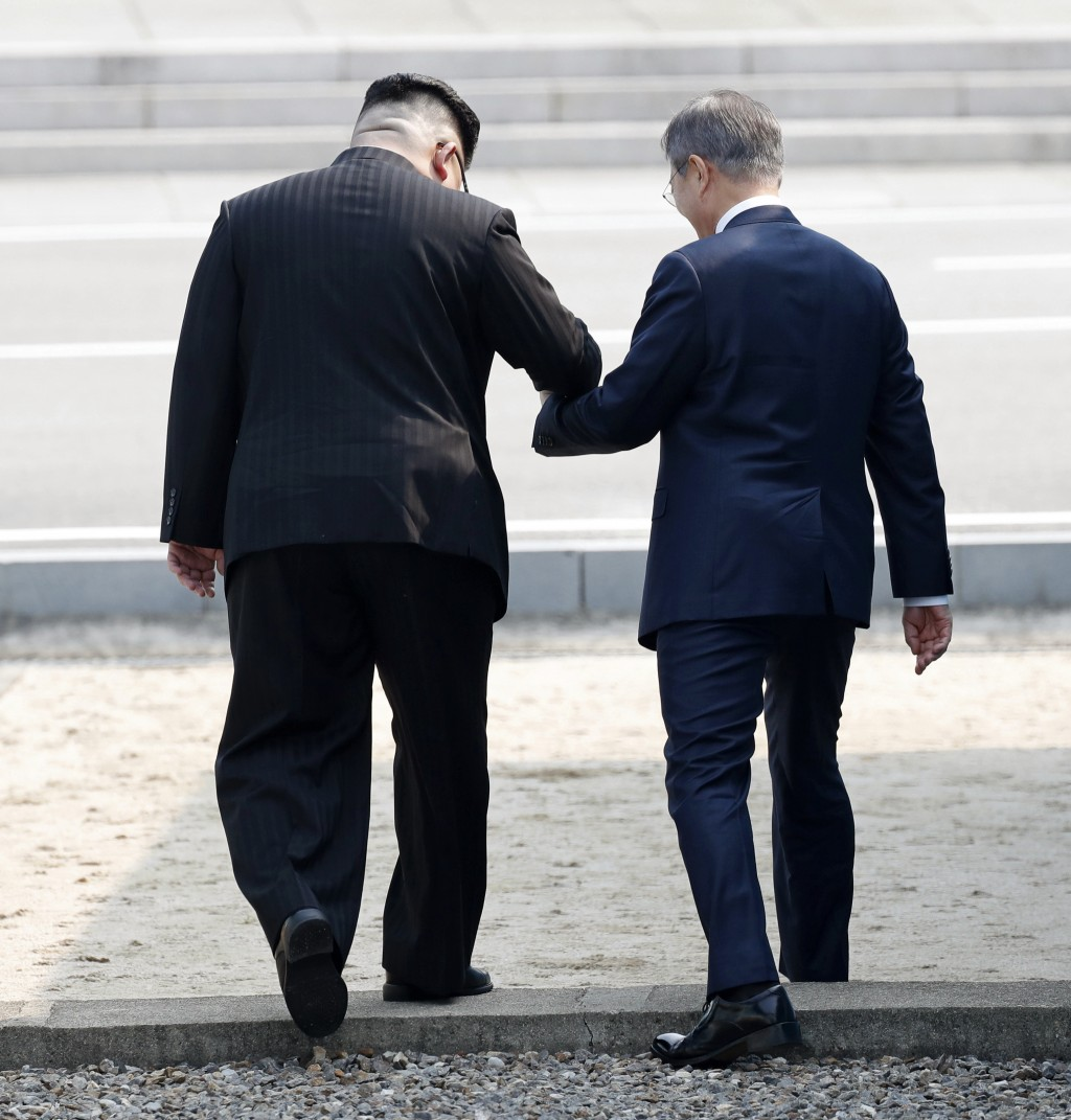 North Korean leader Kim Jong Un, left, and South Korean President Moon Jae-in, right, cross the military demarcation line to the North side at the bor...