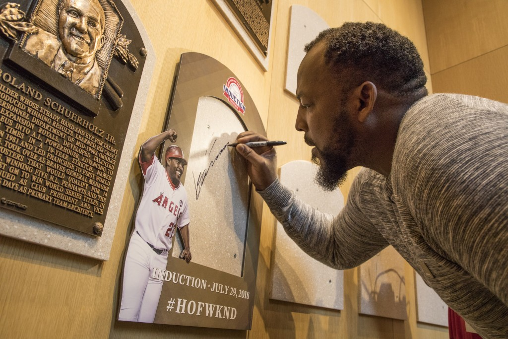Vladimir Guerrero signs the spot where his Baseball Hall of Fame plaque will hang during a visit to the hall, Thursday, April 26, 2018, in Cooperstown...