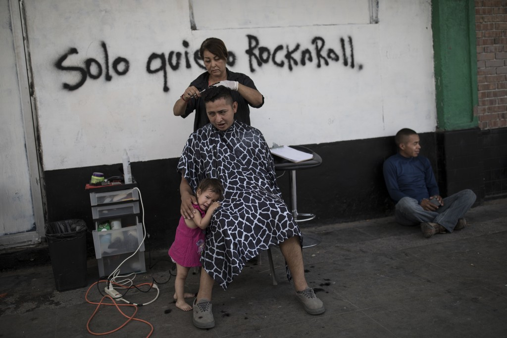 A father from Honduras gets a free haircut while his daughter cries at his lap, at the Alfa & Omega migrant shelter in Mexicali, Mexico, Thursday, Apr...