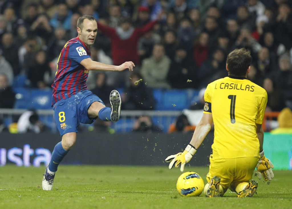 FILE - In this Saturday, Dec. 10, 2011 file photo FC Barcelona's Andres Iniesta faces Real Madrid's goalkeeper Iker Casillas, right, during their Span...