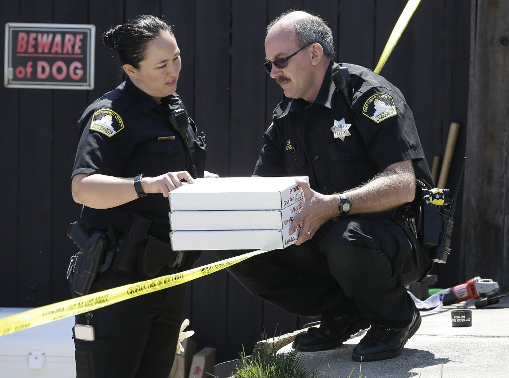 T. Abbott, left, and John Lopes, right, from the Sacramento County Sheriff's crime scene investigation office, conference about boxes of evidence gath...