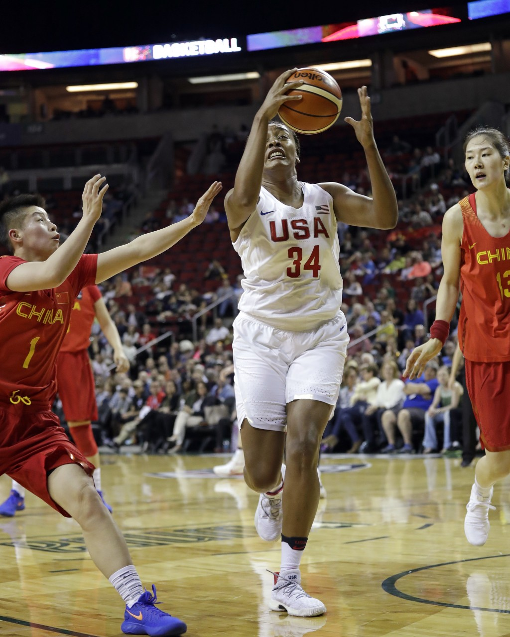 United States' Morgan Tuck (34) drives between China's Yuan Li (1) and Mengran Sun in the first half of an exhibition basketball game Thursday, April ...