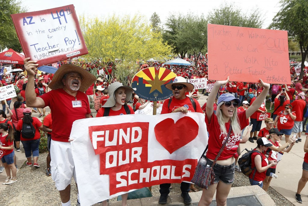 Thousands chant as they participate in a protest at the Arizona Capitol for higher teacher pay and school funding on the first day of a state-wide tea...