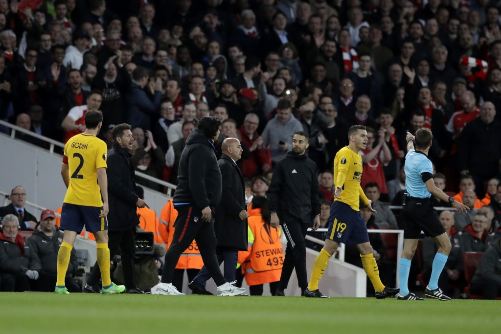 French referee Clement Turpin, far right, asks from Altetico's head coach Diego Simeone, second left, to leave the pitch during the Europa League semi...
