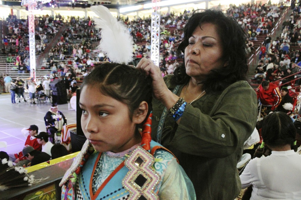 FILE - In this April 24, 2015, file photo, Yvonne Grinnell, right, attaches a feather to Tasia Pecos' hair in preparation for the grand entrance at th...