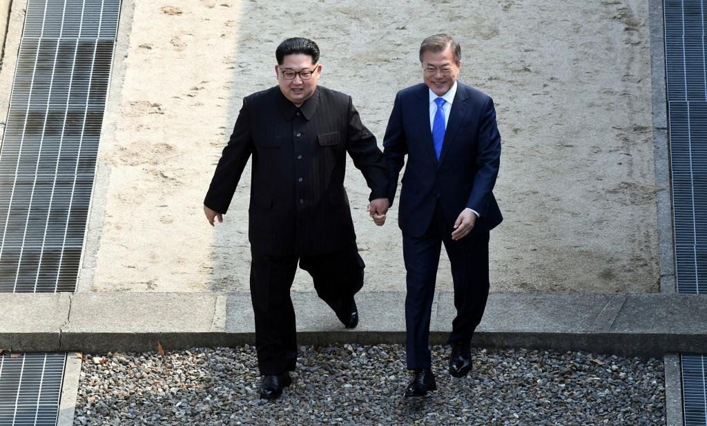 North Korean leader Kim Jong Un, left, and South Korean President Moon Jae-in cross the military demarcation line at the border village of Panmunjom i...