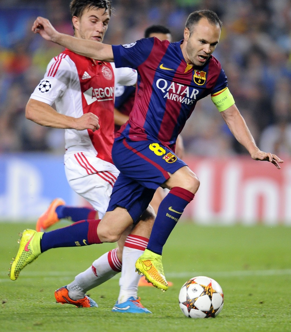 FILE - In this Tuesday, Oct. 21, 2014 file photo Barcelona's Andres Iniesta, centre, tries to take the ball through the Ajax defense during the Champi...