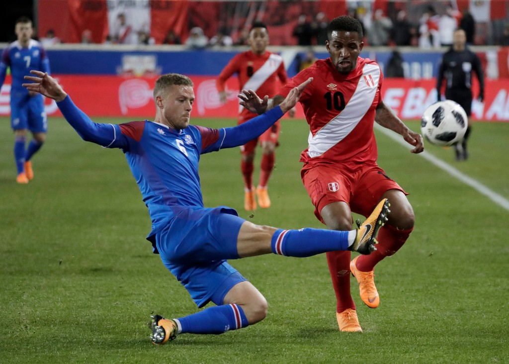 In this photo taken on Tuesday, March 27, 2018, Iceland defender Ragnar Sigurdsson, left, clears the ball as Peru forward Jefferson Farfan attacks dur...