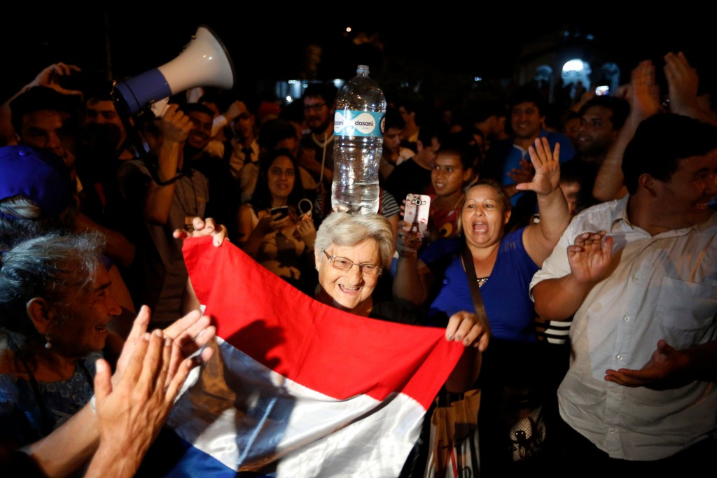 In this April 24, 2018 photo, a woman balances a bottle of water on her head as she performs a traditional dance during a gathering by supporters of p...