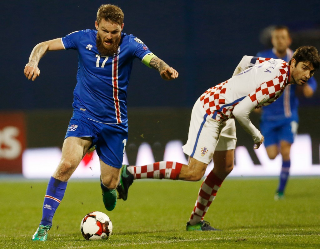 FILE - In this Saturday, Nov. 12, 2016 file photo, Iceland's Aron Gunnarsson, left, is challenged by Croatia's Vedran Corluka during the World Cup Gro...