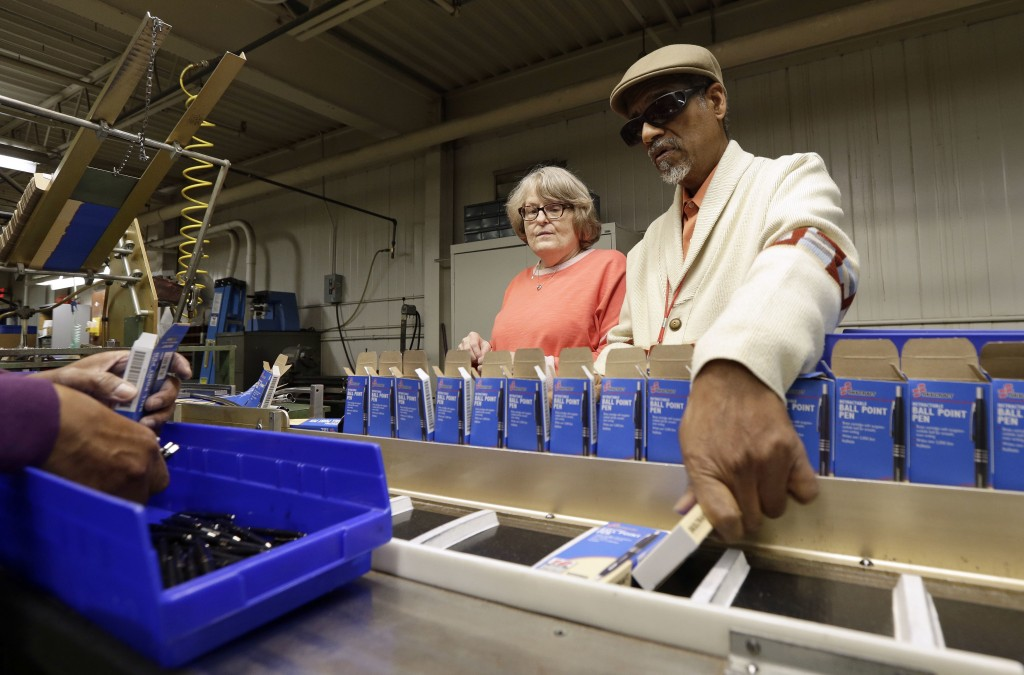 In this Monday, April 16, 2018, photo, employees Lynn Larsen, left, and Clifford Alexander Sr. box SKILCRAFT pens for the U.S. Government at the Indus...