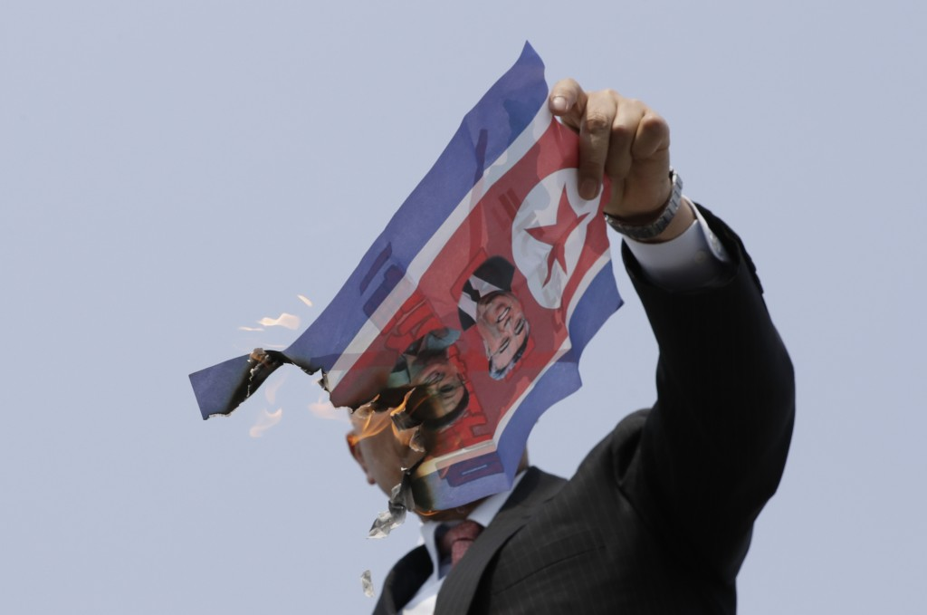 In this Friday, April 27, 2018, file photo, a man burns a North Korean flag with photos of North Korean leader Kim Jong Un, the late leaders Kim Jong ...