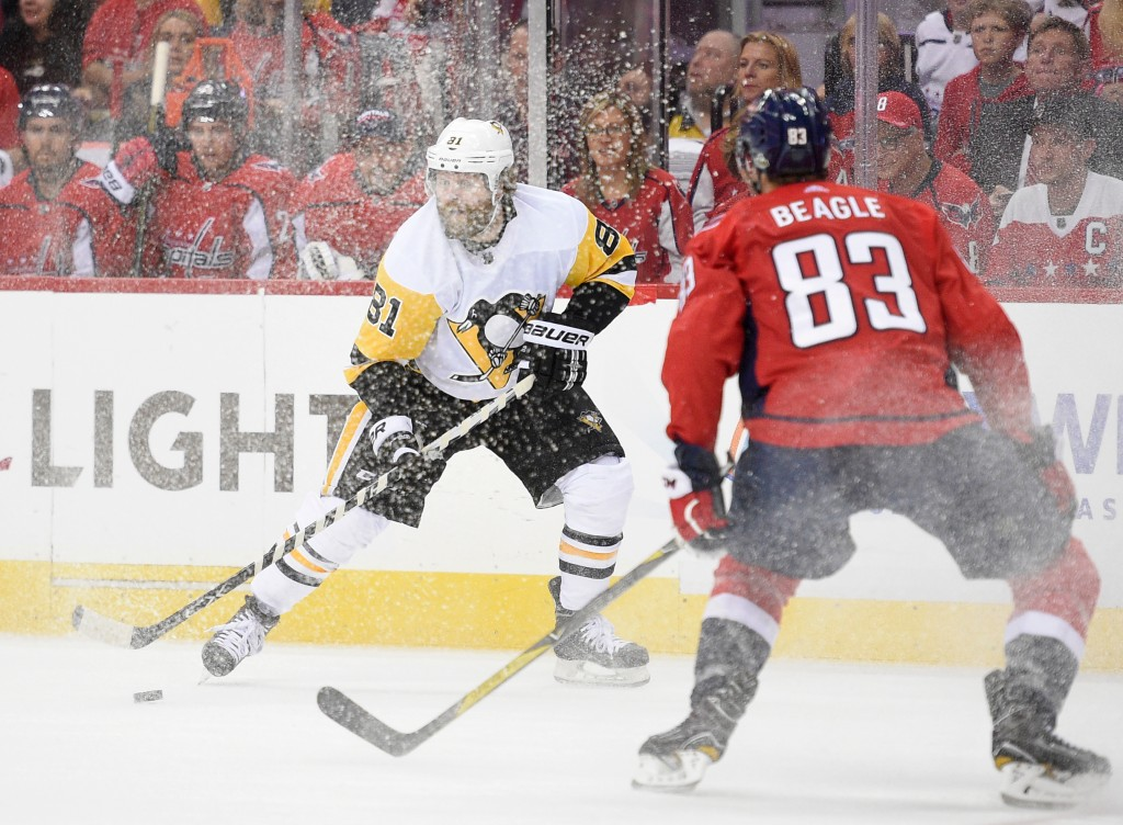 Pittsburgh Penguins right wing Phil Kessel (81) skates with the puck as is shavings are sprayed, while Washington Capitals center Jay Beagle (83) watc...