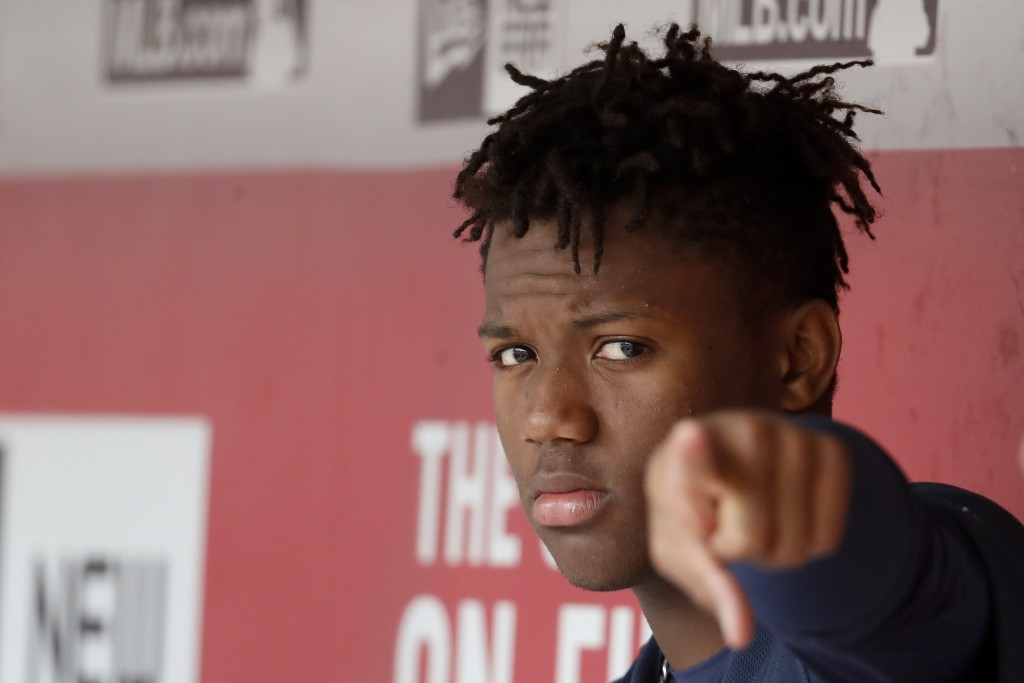 Atlanta Braves center fielder Ronald Acuna Jr. points to the camera while sitting in the dugout in the ninth inning of a baseball game against the Atl...