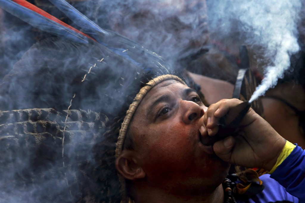 In this April 25, 2018 photo, a Pataxo indigenous man smokes a traditional pipe during a protest against the government's decision to not recognize th...
