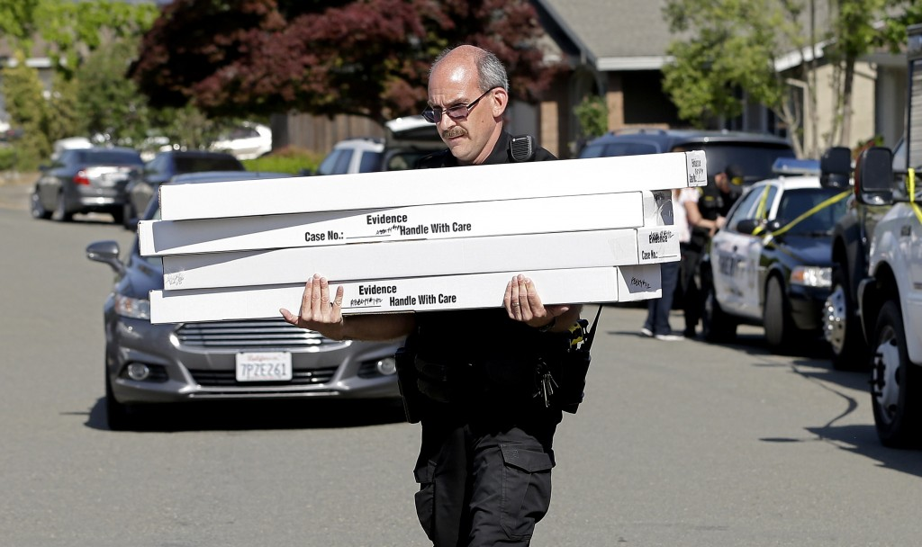 John Lopes, a crime scene investigator for the Sacramento County Sheriff's office, carries boxes of evidence taken from the home of murder suspect Jos...