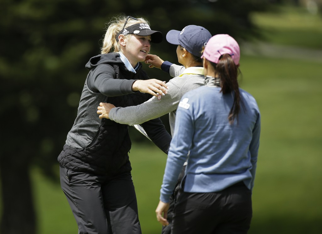 Jessica Korda, left, is greeted by playing partners Azahara Munoz, center, of Spain, and In-Kyung Kim, right, of South Korea, on the ninth green of th...