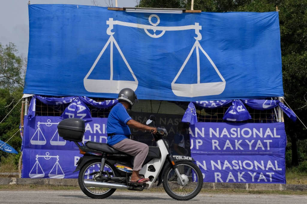 A motorcyclist rides past the flag of Malaysia's ruling National Front coalition, or Barisan Nasional in Pekan, Malaysia, Friday, April 27, 2018. Mala...