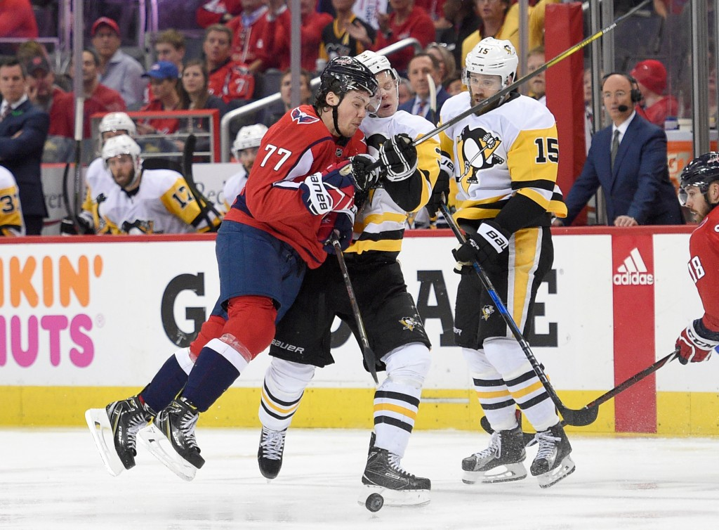 Washington Capitals right wing T.J. Oshie (77) hits Pittsburgh Penguins defenseman Olli Maatta, center, of Finland, during the second period in Game 1...