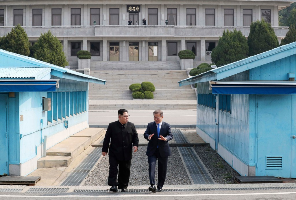 North Korean leader Kim Jong Un, left, listens to South Korean President Moon Jae-in while walking together at the Panmunjom in the Demilitarized Zone...
