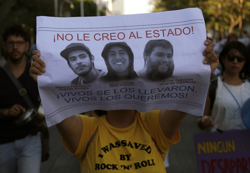 """A student holds a sign with the portraits of three film students who have become emblematic of Mexico's missing, which reads in Spanish: """"I don't beli..."""