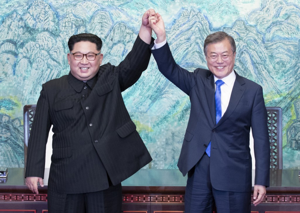 In this Friday, April 27, 2018, file photo, North Korean leader Kim Jong Un, left, and South Korean President Moon Jae-in raise their hands after sign...