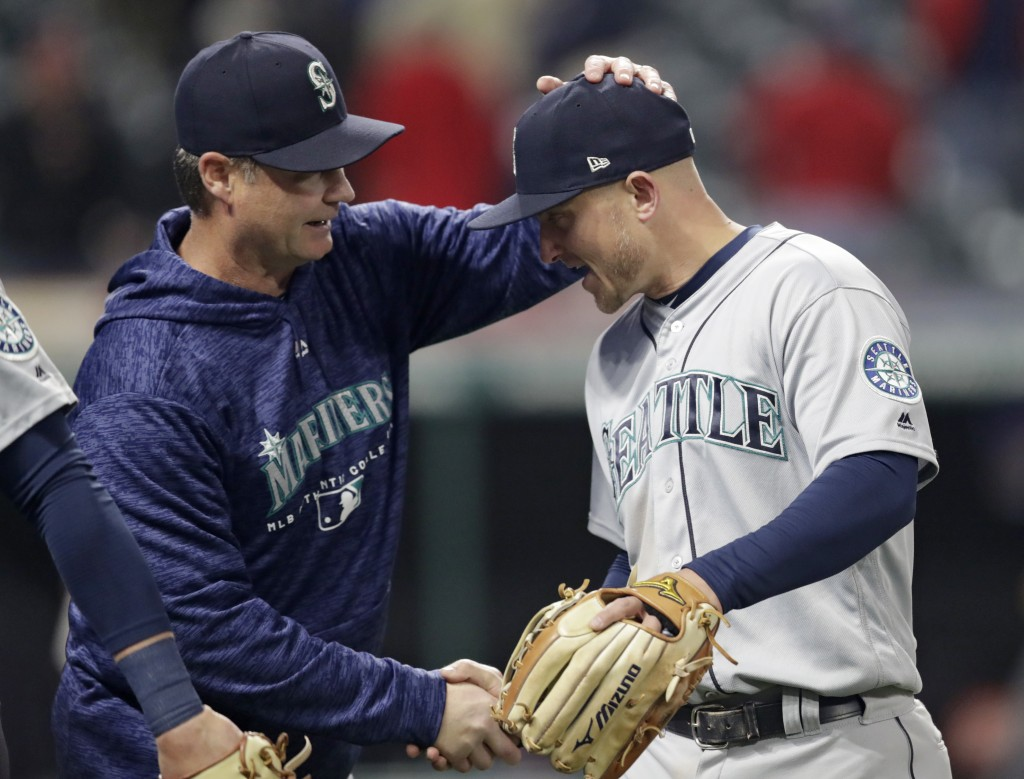 Seattle Mariners manager Scott Servais, left, congratulates Kyle Seager after the Mariners defeated the Cleveland Indians 5-4 in a baseball game, Thur...