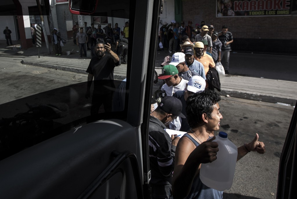 Migrants in a caravan of Central American asylum-seekers board a bus in Mexicali, Mexico, Thursday, April 26, 2018, for a two-hour drive to Tijuana to...
