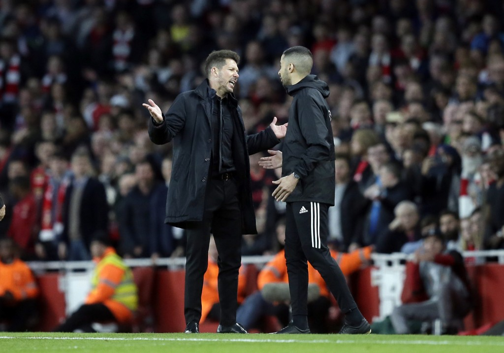 Atletico coach Diego Simeone, left, talks to an assistant referee during the Europa League semifinal first leg soccer match between Arsenal FC and Atl...