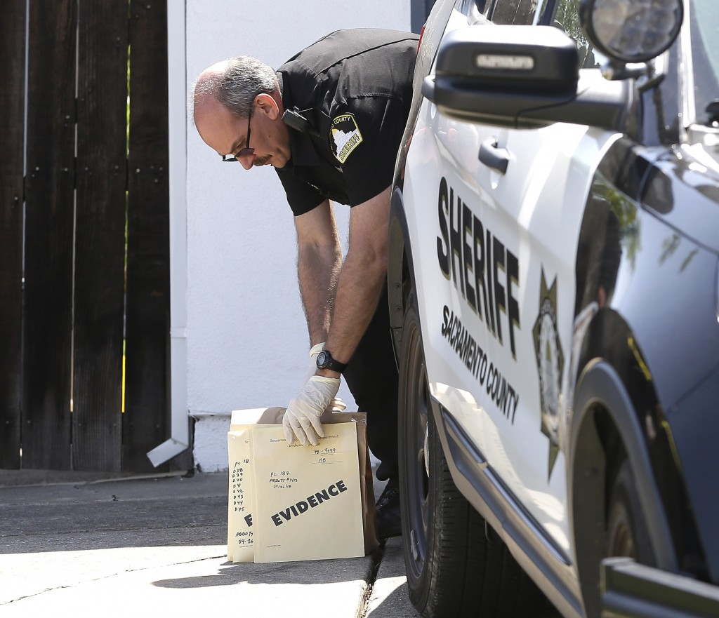 John Lopes, a crime scene investigator for the Sacramento Sheriff's office picks up bags of evidence taken from the home of murder suspect Joseph DeAn...