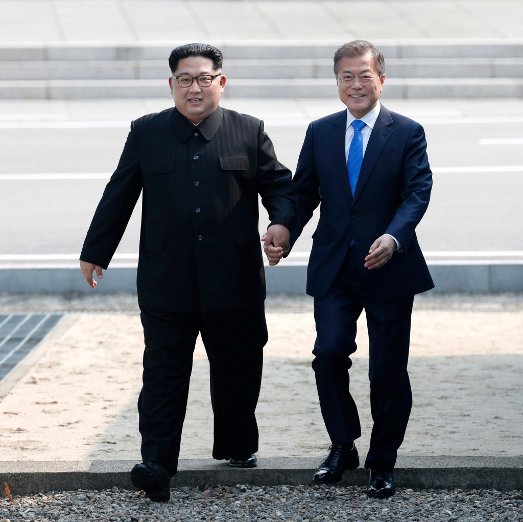 North Korean leader Kim Jong Un, left, and South Korean President Moon Jae-in cross the military demarcation line to the South side at the border vill...
