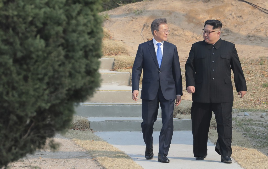 North Korean leader Kim Jong Un, right, and South Korean President Moon Jae-in stroll together at the border village of Panmunjom in the Demilitarized...