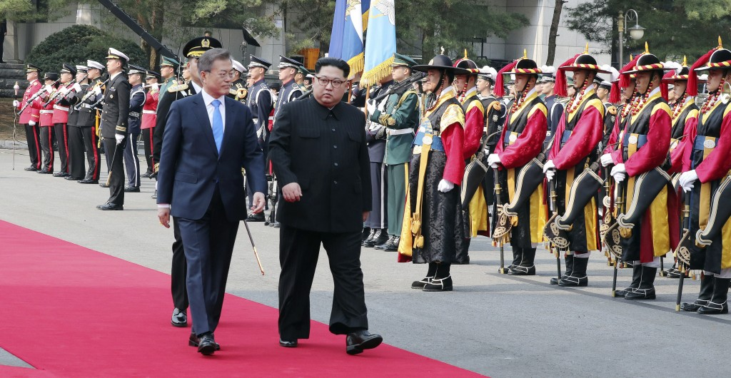 North Korean leader Kim Jong Un, second from left, and South Korean President Moon Jae-in, left, inspect an honor guard after Kim crossed the border i...