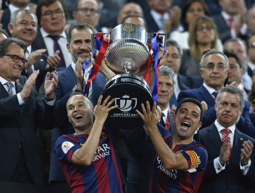 FILE - In this Saturday, May 30, 2015 file photo Barcelona's Andres Iniesta, left, and Xavi Hernandez lift the trophy after winning the final of the C...