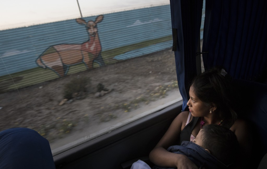 A Central American migrant holding her child looks at the border wall as she arrives by bus with a caravan of migrants to Tijuana, Mexico, Thursday, A...