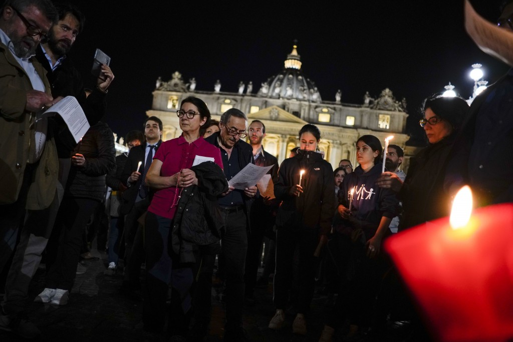 People hold candles as they attend a prayer vigil for terminally ill toddler Alfie Evans, in St. Peter's Square at the Vatican, Thursday, April 26, 20...