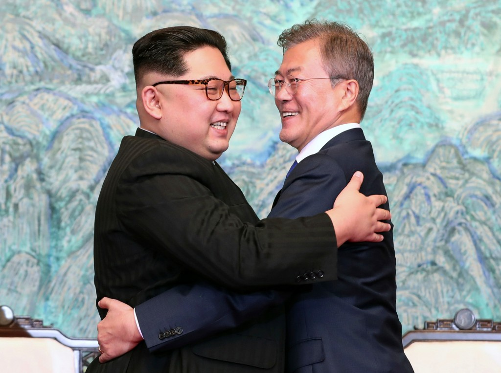 North Korean leader Kim Jong Un, left, and South Korean President Moon Jae-in embrace each other after signing on a joint statement at the border vill...