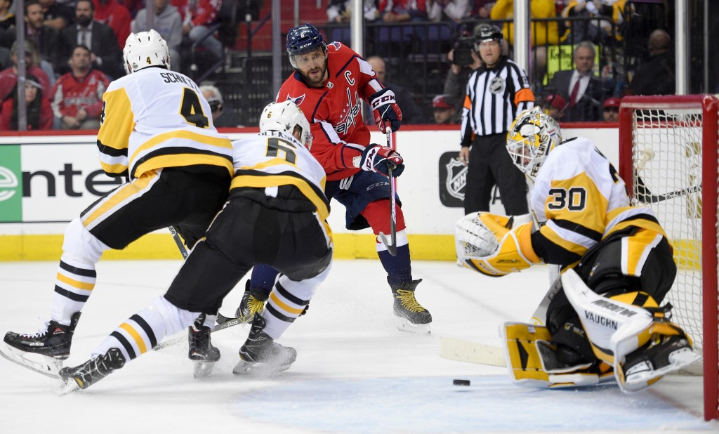 Washington Capitals left wing Alex Ovechkin, second from right, of Russia, watches his shot against Pittsburgh Penguins goaltender Matt Murray (30), d...