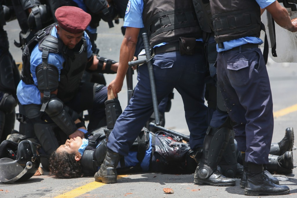 In this April 20, 2018 photo, riot police tend to a fellow officer who was wounded in the leg after a homemade mortar fired by protesters struck her, ...