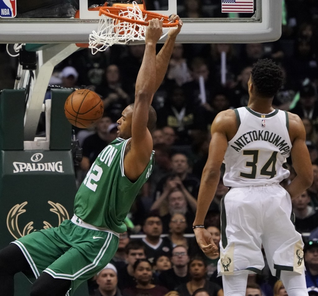 Milwaukee Bucks' Giannis Antetokounmpo watches Boston Celtics' Al Horford dunk during the first half of Game 6 of an NBA basketball first-round playof...