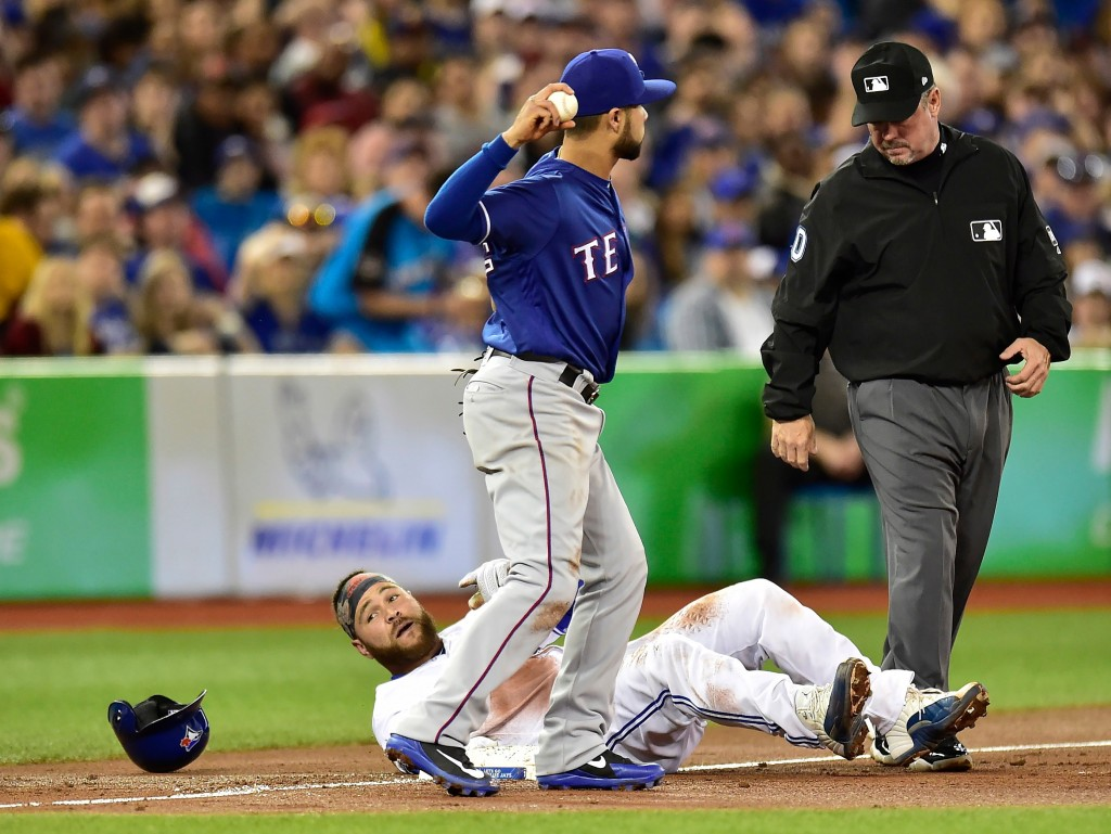 Toronto Blue Jays' Russell Martin sits on third base after being called out during the second inning of the team's baseball game against the Texas Ran...