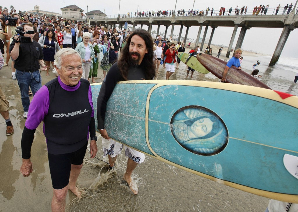 FILE - In this Oct. 3, 2010, file photo, Rev. Matt Munoz, center, heads to the surf with Rev. Christian Mondor, left, during the Blessing of the Waves...