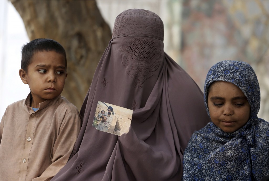 In this Thursday, April 19, 2018 photo, Bashro Bibi, a mother of five shows picture of her missing husband in Peshawar, Pakistan. A Pakistani rights g...