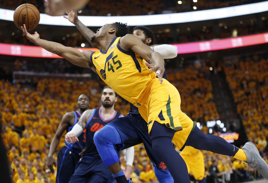 Utah Jazz guard Donovan Mitchell (45) puts up a shot as Oklahoma City Thunder forward Paul George, rear, defends in the second half during Game 6 of a...