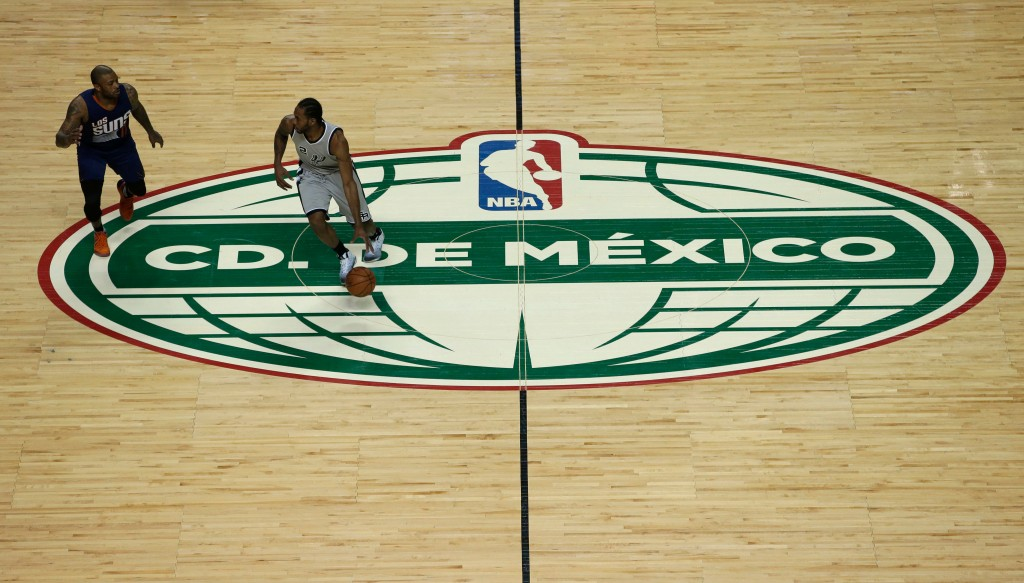 FILE - In this Jan. 14,2017, file photo, San Antonio Spurs Kawhi Leonard dribbles the ball past the middle of the court as Phoenix Suns P.J. Tucker fo...