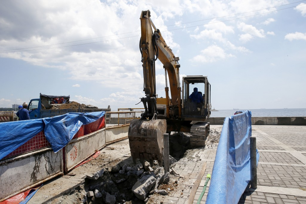 """A backhoe scoops earth from the spot where a statue of a """"Comfort Woman"""" or Filipino sex slave during WWII was erected along a scenic Baywalk in Manil..."""