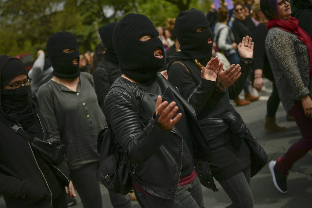 Masked women shout slogans during a protest against sexual abuse in Pamplona, northern Spain, Saturday, April 28, 2018. Women's rights groups protest ...
