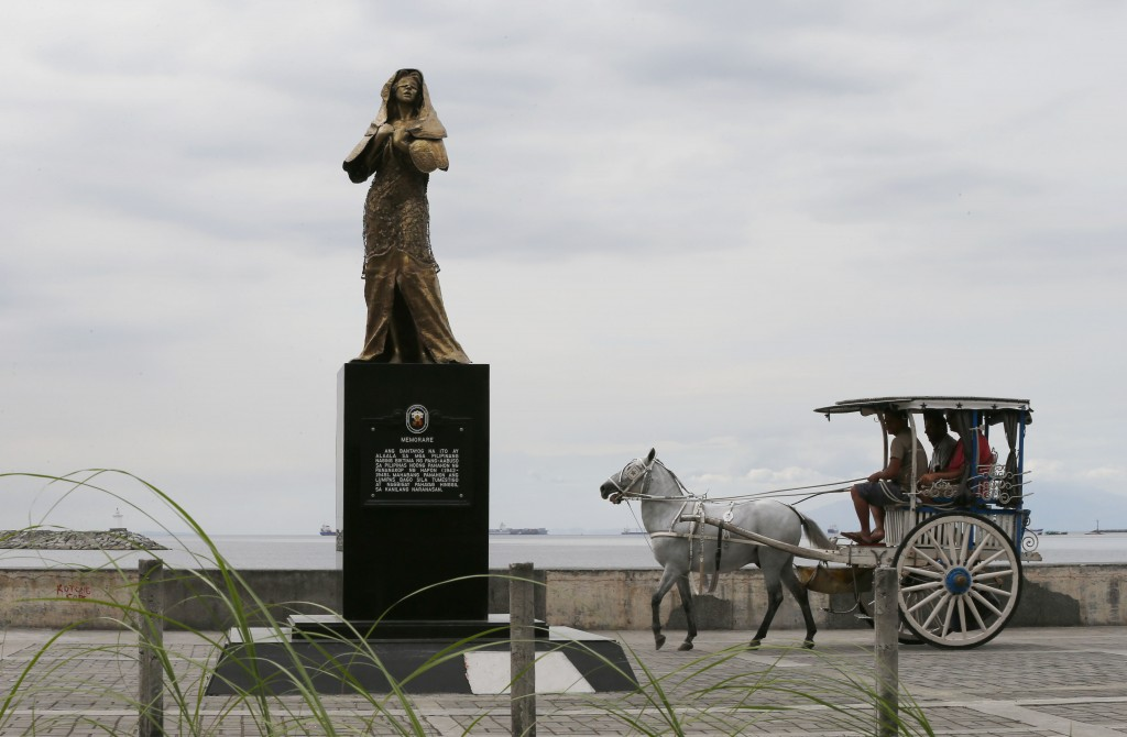 """FILE - In this Jan. 11, 2018 file photo, a horse-drawn cart, catering to tourists, passes by a statue of a """"Comfort Woman"""" or alleged Filipino sex sla..."""