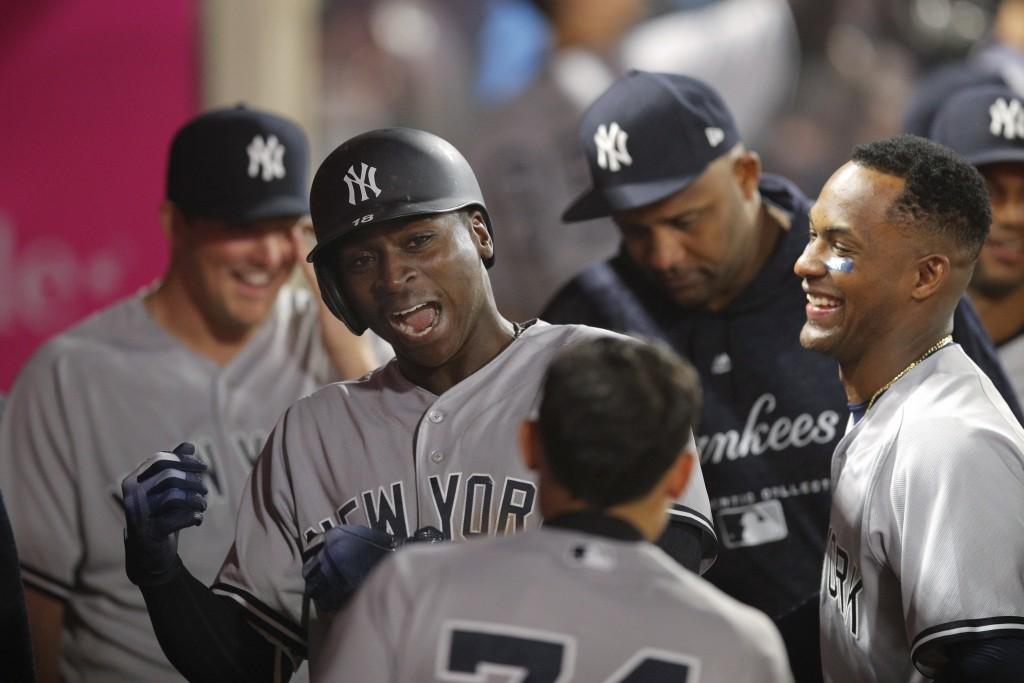 New York Yankees' Didi Gregorius, second from left, celebrates his home run with teammates during the 10th inning of a baseball game against the Los A...